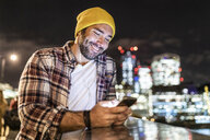 UK, London, smiling man leaning on a railing and looking at his phone with city lights in background - WPEF01217