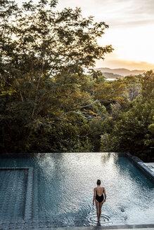 Philippines, Palawan, Coron, woman in swimming pool in the evening - DAWF00765