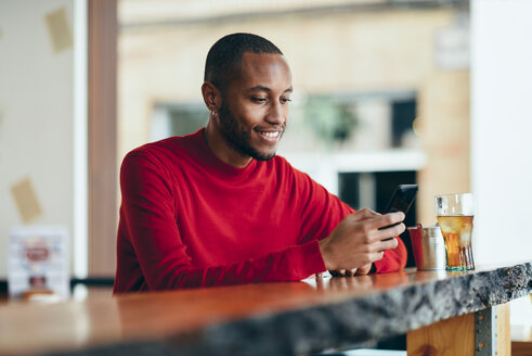 Smiling young man wearing red pullover at counter of a bar with soft drink and mobile phone - JSMF00697