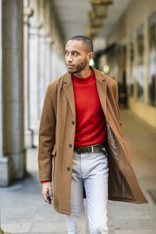 Fashionable young man wearing red pullover and brown coat walking along arcade - JSMF00706