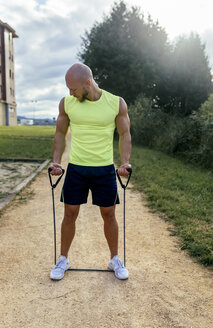 Muscular man exercising with expander outdoors - MGOF03844