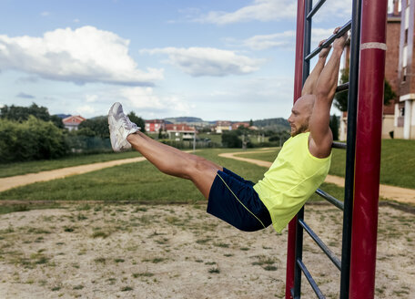 Muscular man exercising at a climbing frame outdoors - MGOF03847