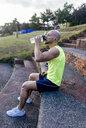 Muscular man having a break from exercising drinking water - MGOF03850