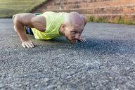 Muscular man doing push-ups outdoors - MGOF03859