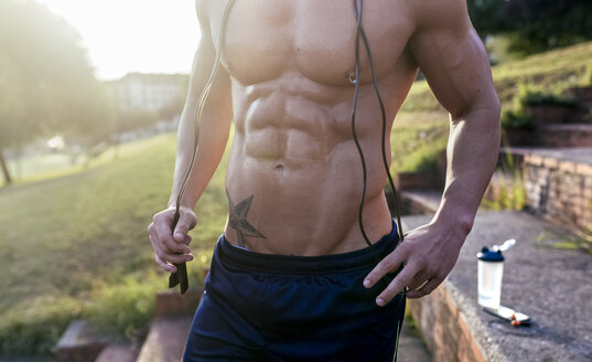 Mid-section of barechested muscular man with skipping rope outdoors - MGOF03874
