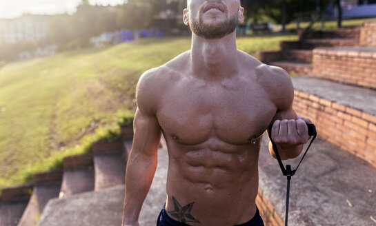 Mid-section of barechested muscular man exercising with expander outdoors - MGOF03877