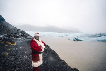 Iceland, smiling Santa Claus standing in front of glacier - OCMF00175