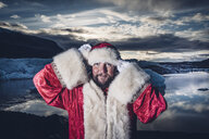 Iceland, portrait of Santa Claus standing in front of glacier - OCMF00178