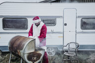Iceland, Santa Claus standing in front of caravan barbecueing - OCMF00181