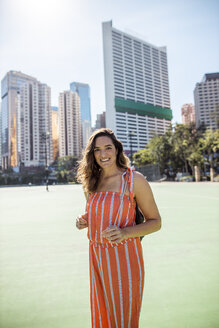 Hong Kong, Causeway Bay, Victoria Park, portrait of smiling woman on a sports field - DAWF00777