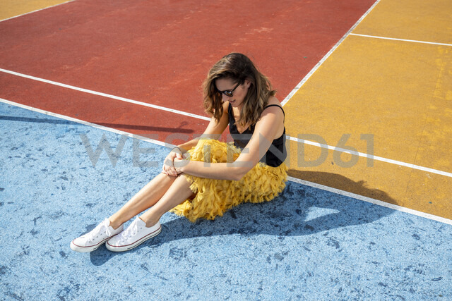 Woman wearing sunglasses sitting at a sports field - DAWF00792
