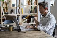 Businessman holding coffee mug using laptop at desk - GIOF05063