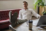 Portrait of businessman sitting with feet on desk - GIOF05066