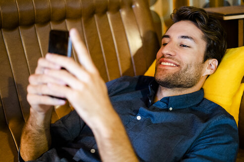 Man lying on couch using cell phone - GIOF05078