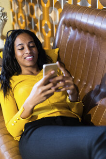 Smiling woman lying on couch in vintage living room using cell phone - GIOF05087