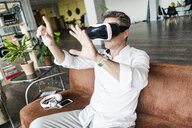 Mature man wearing VR glasses sitting on couch in a loft - GIOF05096