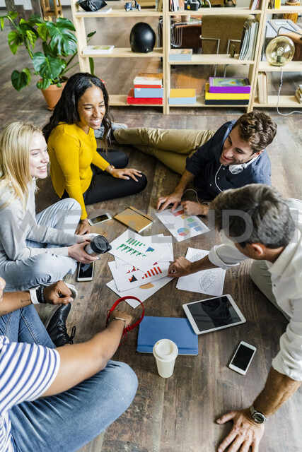Happy business team sitting on floor discussing documents in loft office - GIOF05117 - Giorgio Fochesato/Westend61