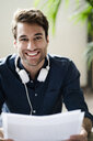 Portrait of smiling young man with headphones holding papers - GIOF05135