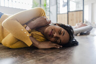 Smiling young woman lying on wooden floor with closed eyes - GIOF05141