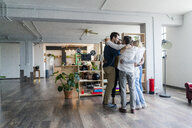 Business team huddling in loft office - GIOF05147