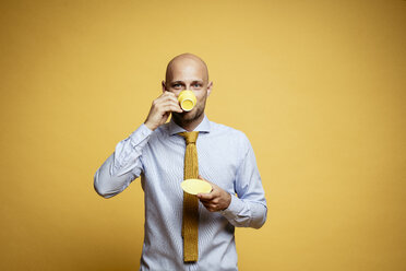 Portrait of bald businessman drinking cup of coffee against yellow background - DAWF00826