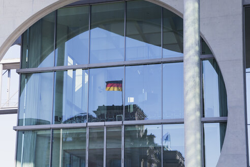Germany, Berlin, Regierungsviertel, reflection of Reichstag building and German Flag in Marie-Elisabeth-Lueders-Building, mirroring in glass facade - GWF05694
