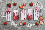 Homemade strawberry coconut ice lollies with fresh strawberries and coconut slices on granite - GWF05710