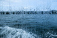 View through a rain spattered window over water and a boat's wake on an overcast day. - MINF09823