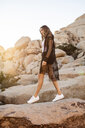 USA, California, Los Angeles, smiling woman walking on rocks in Joshua Tree National Park - DAWF00847