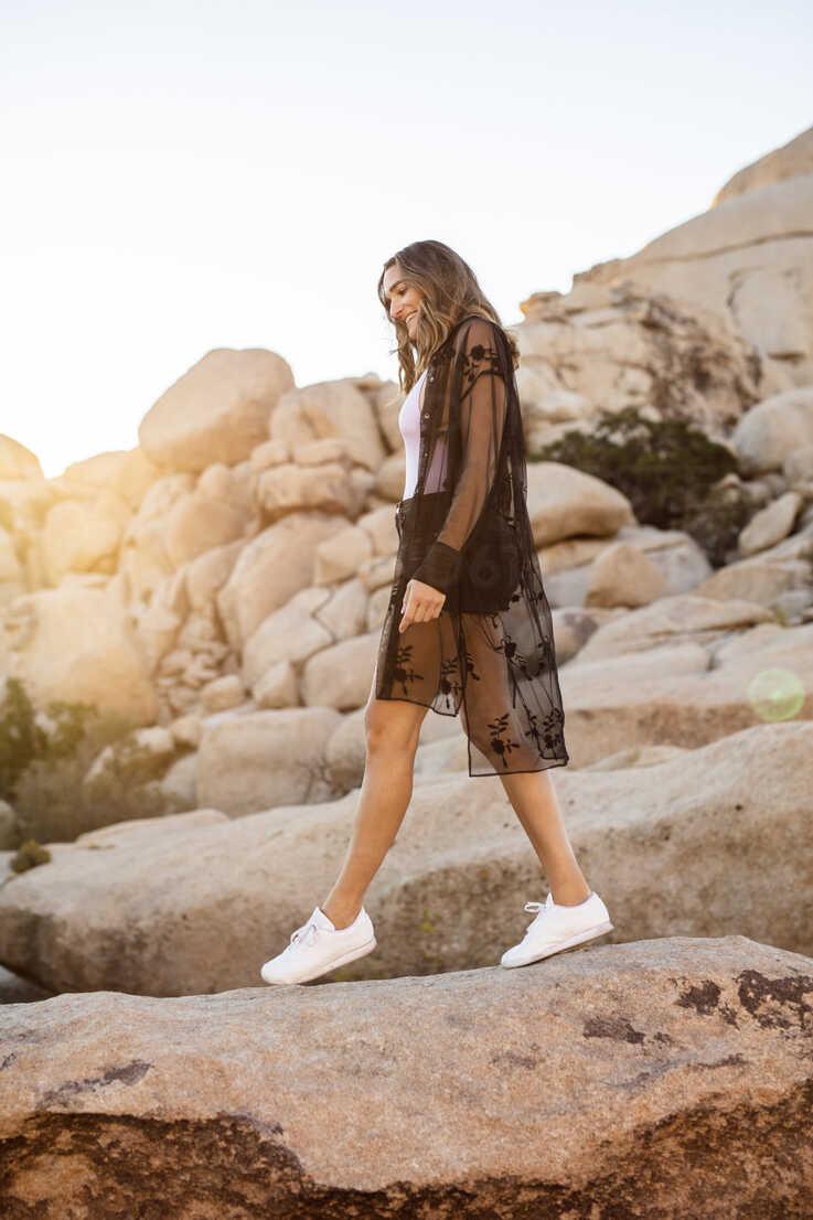 USA, California, Los Angeles, smiling woman walking on rocks in Joshua Tree National Park - DAWF00847 - Daniel Waschnig Photography/Westend61
