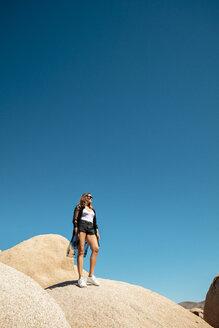 USA, California, Los Angeles, woman standing on rock under blue sky in Joshua Tree National Park - DAWF00859