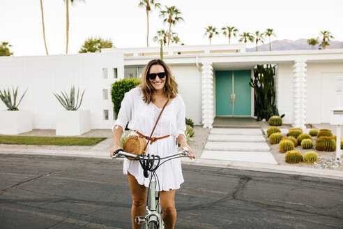 USA, California, Palm Springs, portrait of smiling woman on bicycle on the street - DAWF00865