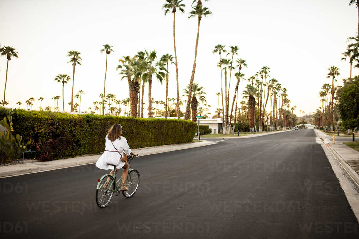 USA, California, Palm Springs, woman riding bicycle on the street - DAWF00868 - Daniel Waschnig Photography/Westend61