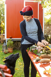 Smiling senior woman with red dyed hair looking at her dog while tinkering autumnal decoration - OJF00292