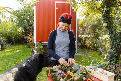 Smiling senior woman with red dyed hair with dog tinkering autumnal decoration in the garden - OJF00295