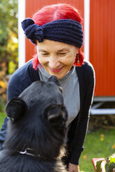 Portrait of smiling senior woman with red dyed hair face to face with her dog in the garden - OJF00298