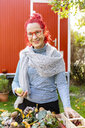 Portrait of smiling senior woman with red dyed hair tinkering autumnal decoration in the garden - OJF00301