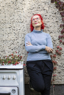 Portrait of smiling senior woman with red dyed hair leaning against house front - OJF00304