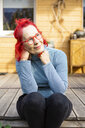 Portrait of smiling senior woman with red dyed hair sitting on terrace in front of her house relaxing - OJF00310