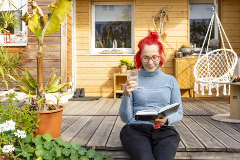 Portrait of smiling senior woman with red dyed hair sitting on terrace in front of her house reading a book - OJF00313