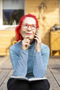 Portrait of smiling senior woman with red dyed hair on the phone sitting on terrace in front of her house - OJF00316