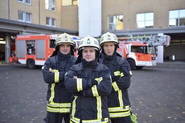 Portrait of three confident firefighters standing on yard in front of fire engine - LYF00844