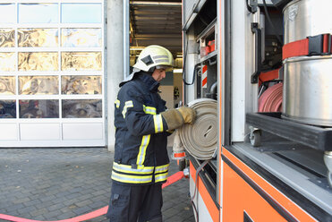 Firefighter taking firehose from fire engine - LYF00850
