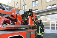 Portrait of two firefighters exercising at fire engine - LYF00853