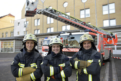 Portrait of three smiling firefighters standing on yard in front of fire engine - LYF00859