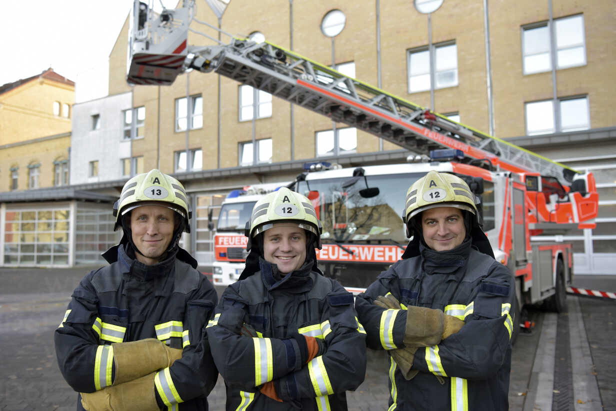 Portrait of three smiling firefighters standing on yard in front of fire engine - LYF00859 - lyzs/Westend61