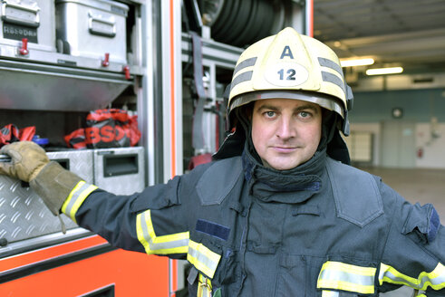 Portrait of confident firefighter in front of fire engine - LYF00862