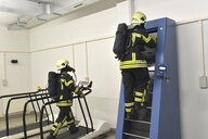 Two firefighters with respirator and air tank exercising in exercise room - LYF00865