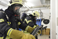 Two firefighters with respirator and air tank exercising on treadmill - LYF00868