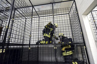 Two firefighters with respirator and air tank exercising - LYF00871